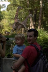 Image of father and son and rated giraffe