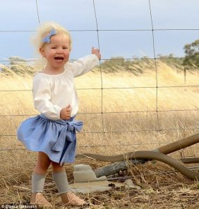 image of Mother's picture of 2-year-old daughter photobombed by massive brown snake