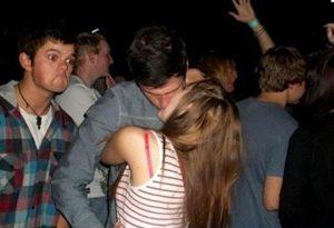 Image of kissing couple photobomb